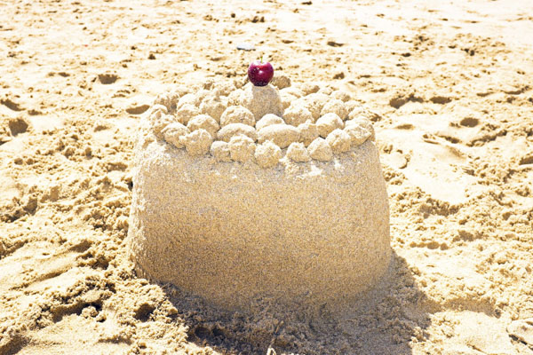 Sand castle with cherry on top
