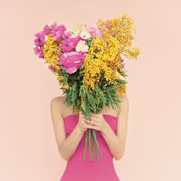 Woman behind bouquet of flowers