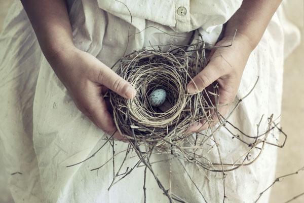 Girl holding nest with blue egg