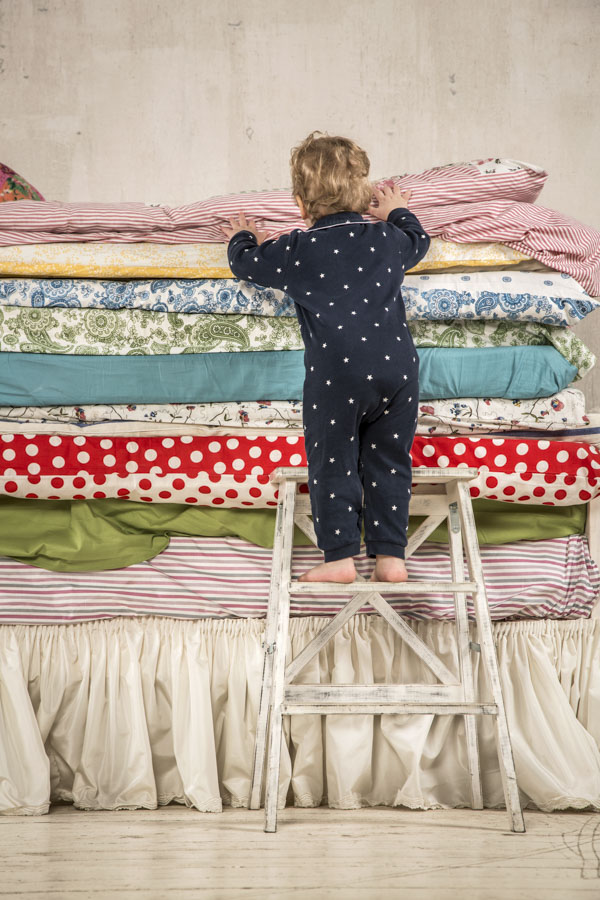 Toddler climbing up onto bed