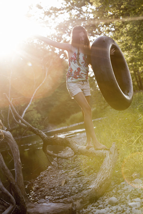 Girl walking on log with inner tube