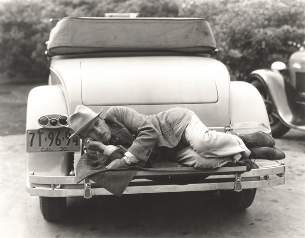 Man sleeping on bumper of car