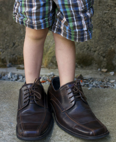Little boy standing in daddy's shoes