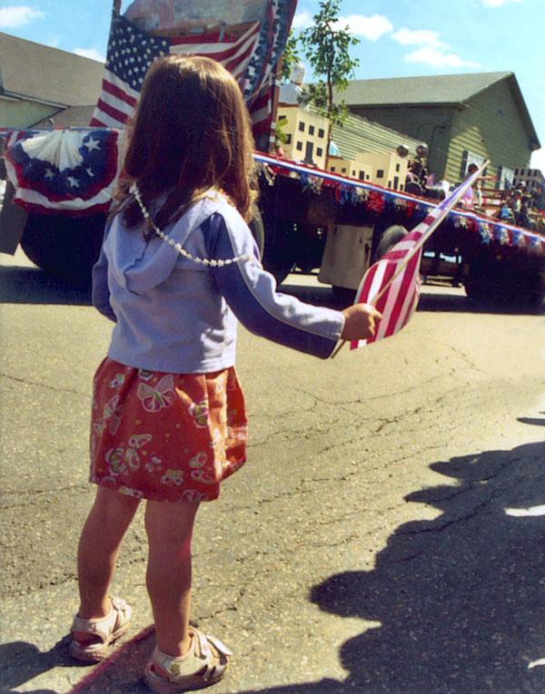 Little girl at parade waving American flag