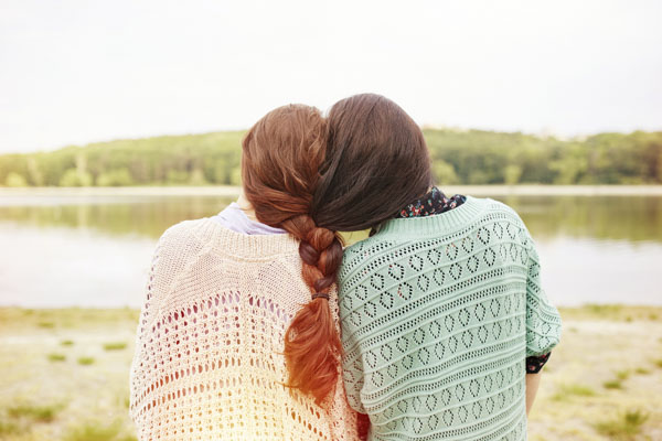 Two sisters with intertwined braids
