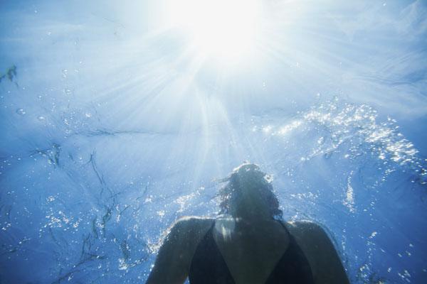 Woman underwater looking up