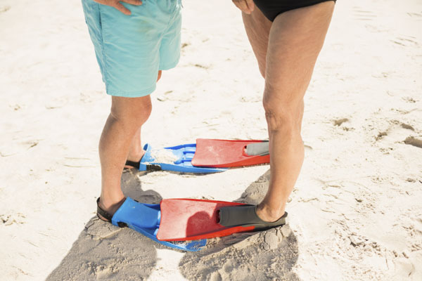 Couple in swim fins standing toe to toe