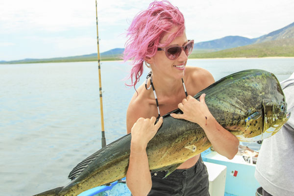 Woman holding dorado (mahi) fish