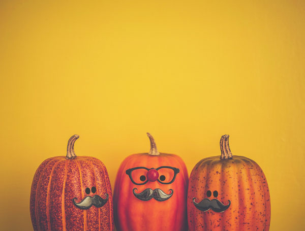 Three pumpkin characters wearing mustaches for Halloween