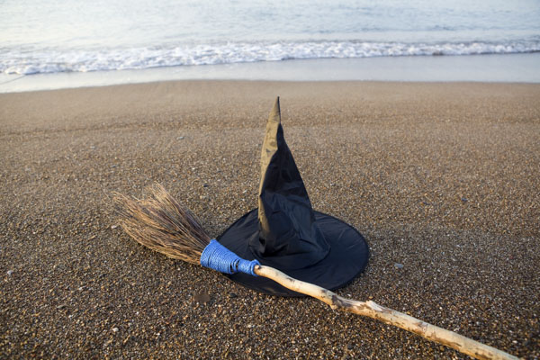Witch hat and broom on beach. Witch in ocean.