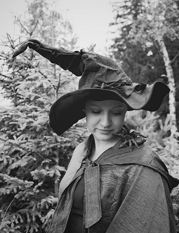Witch smiling at spider on her shoulder