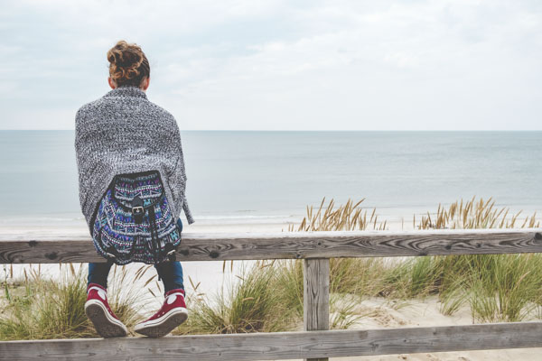 Woman sitting looking out to sea