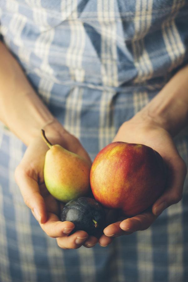 Hands holding fresh organic fruits