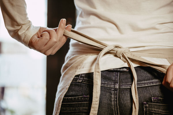 Close Up Of Waitress Hands Tying Apron In Cafe