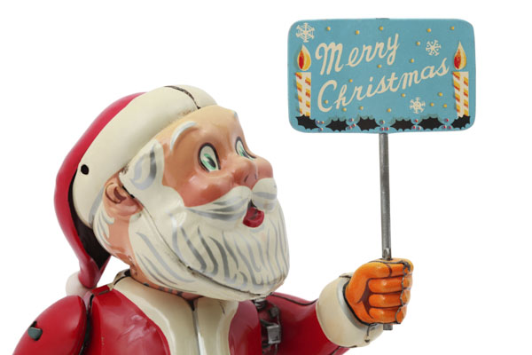 Antique Santa Claus wind-up toy carrying Merry Christmas sign