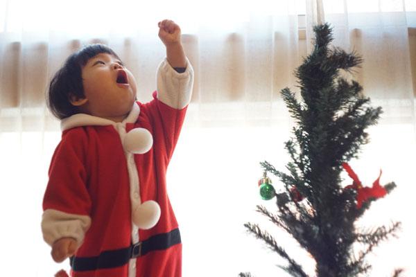 Little girl reaching for star on Christmas tree