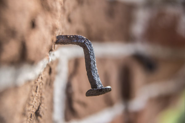 Bent nail in brick wall