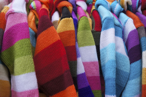 Multi-colored striped sweaters on hangers