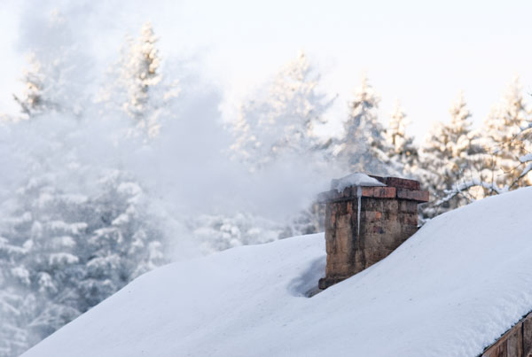 Smoke coming out of snowy cabin
