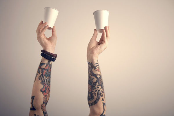 Hands holding empty cups up to be filled