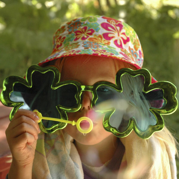 Little girl with shamrock sunglasses blowing bubbles