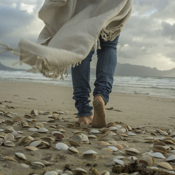 Woman walking barefoot on seashells on beach