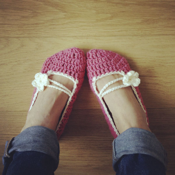 Woman wearing pink knitted slippers with flowers