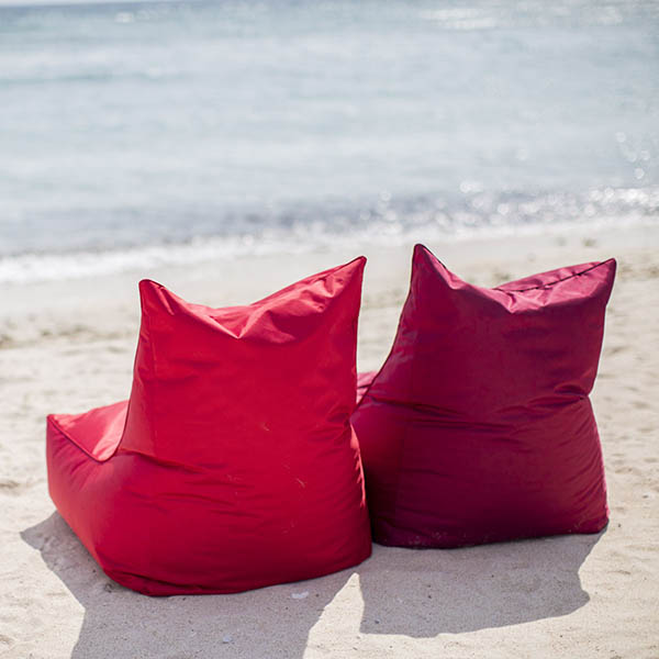 Two red bean bag chairs on the beach