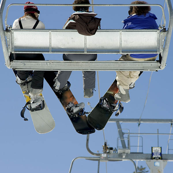 Three snowboarder friends on ski lift