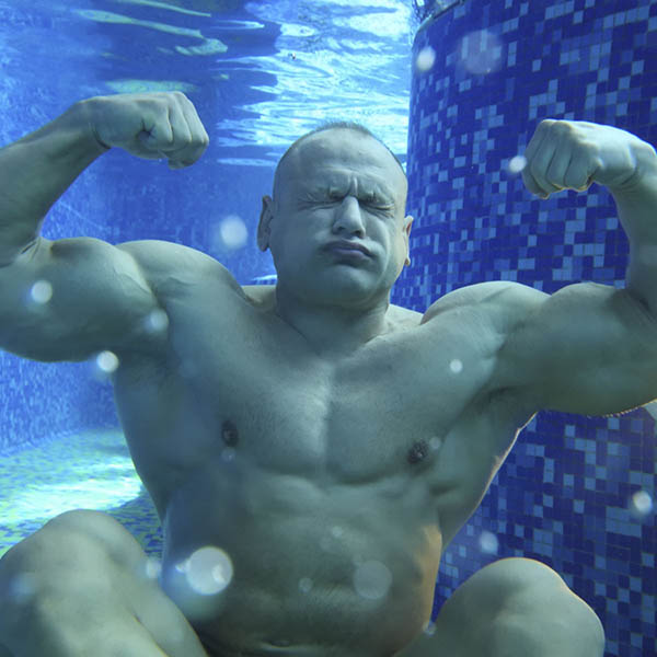Man holding his breath under water and showing muscles