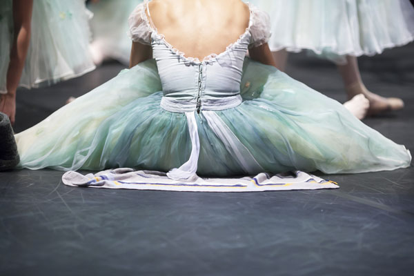 Ballerina sitting off stage waiting to take her turn