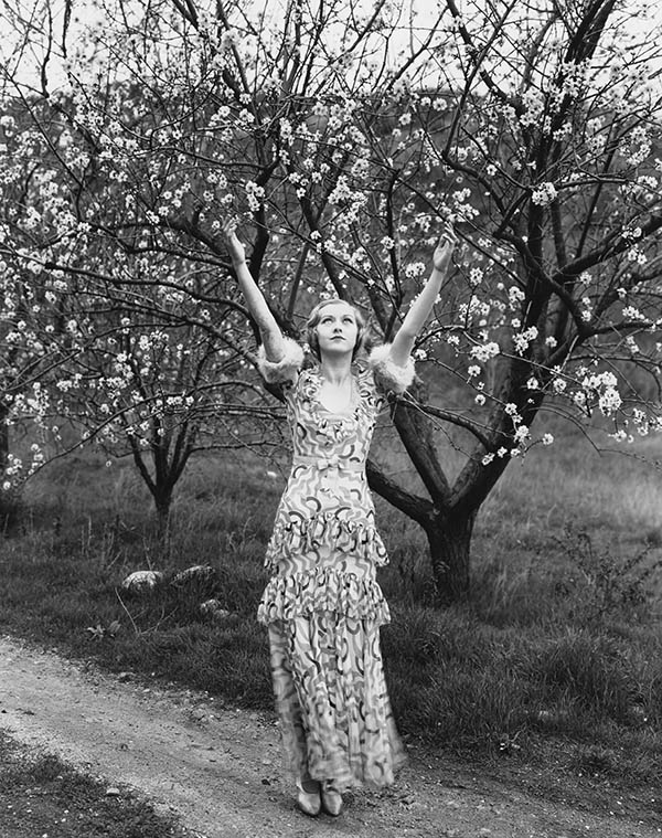 Vintage woman in spring dress arms raised in orchard