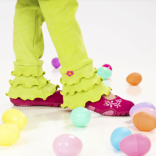 Girl with ruffled lime green pants walking through plastic Easter eggs
