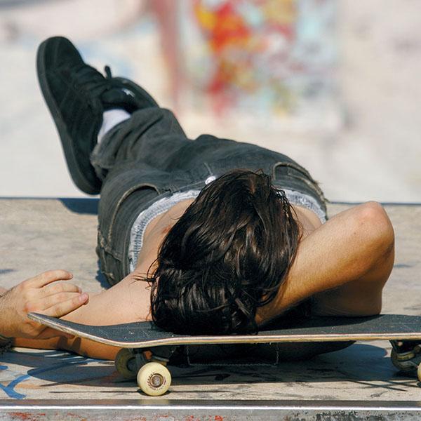 Young man sleeping on skateboard