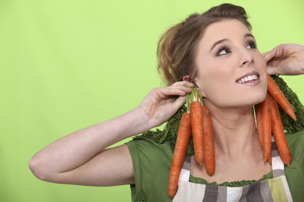 Woman holding carrots up to her ears