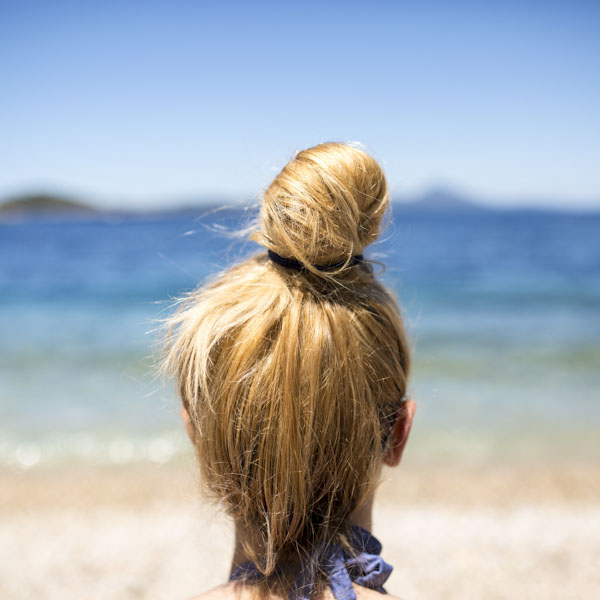 Woman with top knot on beach