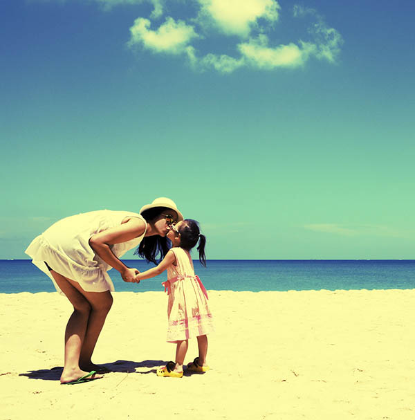 Mother kissing child on beach