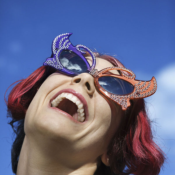 Woman with rhinestone cat's eye sunglasses looking up at sky
