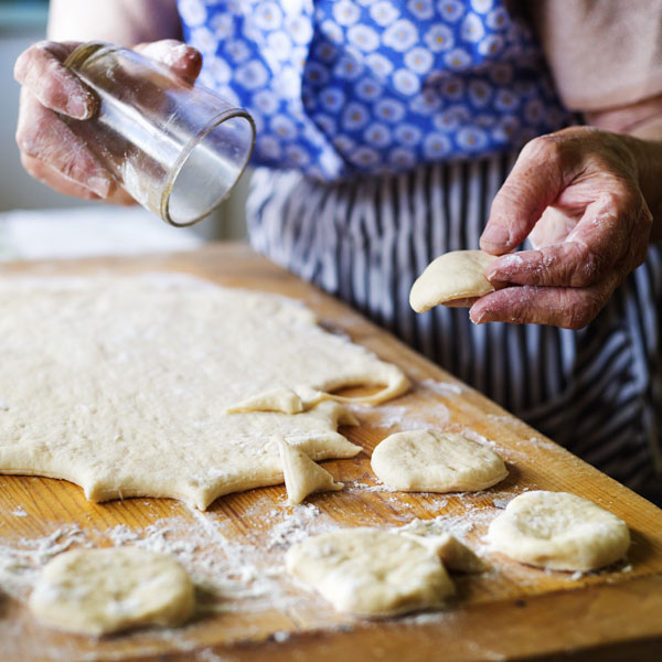 Woman cutting biscuits with glass