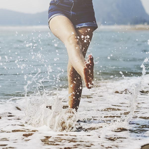 Happy woman kicking up waves
