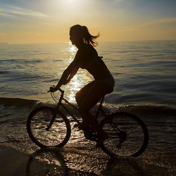 Woman riding her bike on beach at sunset
