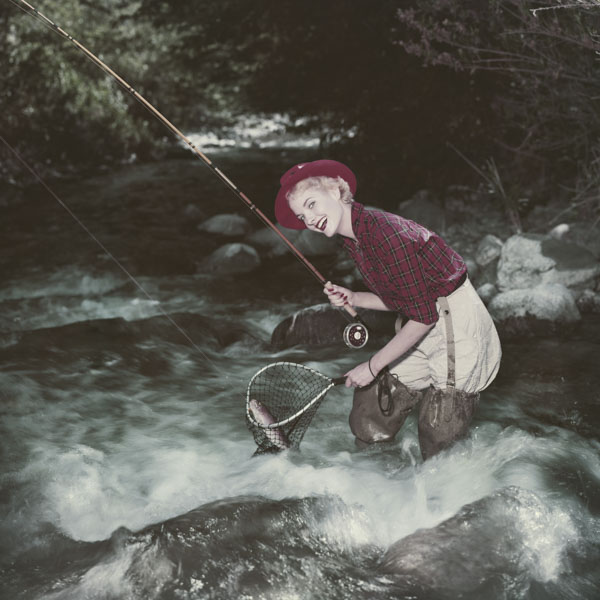 Vintage woman stream fishing with catch in net