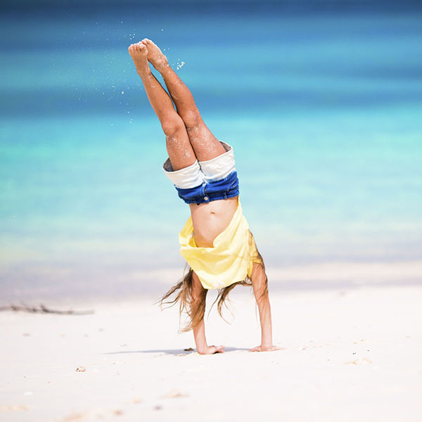 Girl doing handstand on beach and leaning